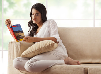 Woman reading a book on a sofa