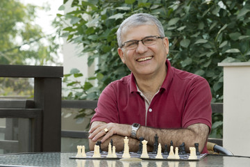 Portrait of senior man smiling while sitting by table with chess board