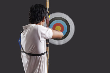 Rear view of man aiming target with bow against black background Rear view of man aiming target with bow against black background