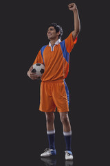 Happy soccer player with ball celebrating victory isolated over black background