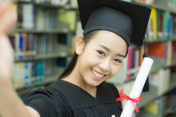 Young Asian Woman Students wearing Graduation hat and gown, Library background, Woman with Graduation Concept. Woman Holding Smartphone for Selfie.
