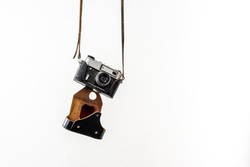 Vintage film camera in a leather case hanging on straps on a white background