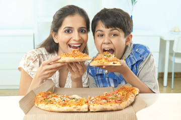 Mother and son eating pizza