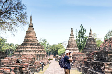 man with backpack taking a photo at Sukhothai  Historical Park,public place in Thailand