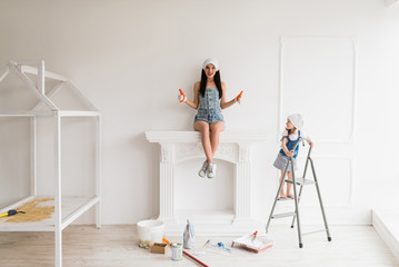 The young smiling mother does repair at home, she sits on fireplace and keeps thumbs up and her daughter stands on ladder and looks at mother Wall mural