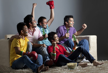 Enthusiastic male friends watching boxing match together at home