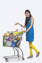Portrait of a woman with a shopping cart gesturing