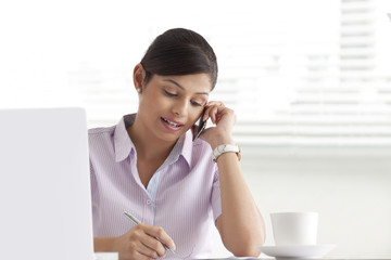 Young businesswoman writing white using cell phone