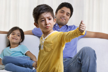 Boy acting in front of father and sister