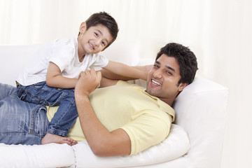 Portrait of father and child on sofa