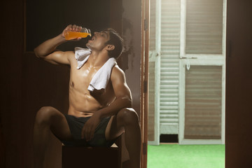 Young man drinking juice in gym