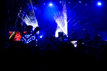 Blur background of concert crowd in front of bright stage lights musics