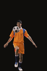 Full length of male soccer player doing kick ups isolated over black background