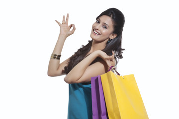 Portrait of a woman with shopping bags giving ok sign