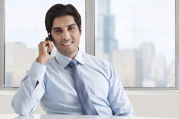 Portrait of smiling businessman speaking on phone call at office