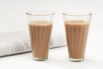 Glasses of chai with newspaper isolated on white background