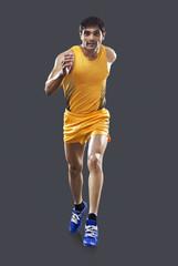 Full length of male runner running over gray background