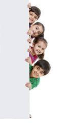 Group of kids hiding behind billboard
