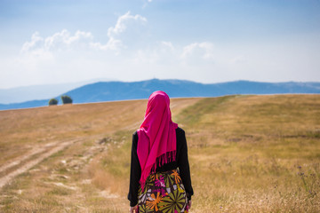 Covered muslim caucasian girl with pink hijab and colorful long skirt standing on a field in summer and looking at the horizon with mountains and blue sky with clouds