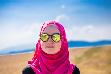 Covered muslim caucasian girl with pink hijab and reflective black and colorful sunglasses portrait standing on a field in summer and looking at the horizon with mountains and blue sky with clouds