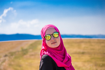 Covered muslim caucasian girl with pink hijab and reflective black and colorful sunglasses posing from side and standing on a field in summer and  with mountains and blue sky with clouds