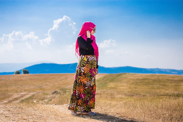 Covered beautiful muslim caucasian girl with pink hijab, colorful long skirt and sunglasses posing from side on grass field in summer with mountains and blue sky with clouds