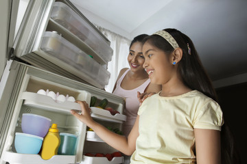Close-up of daughter and mother looking in the fridge