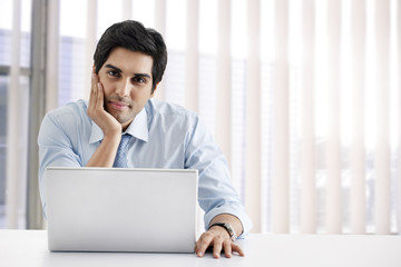 Happy young businessman sitting at his desk with laptop