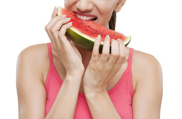 Midsection of a young woman biting watermelon over white background