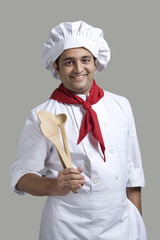 Portrait of a chef with wooden spoons