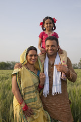 Portrait of a happy Indian family in the field