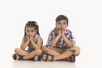 Full length portrait of bored siblings sitting against white background