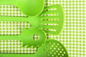 Green utensils on gingham textile background