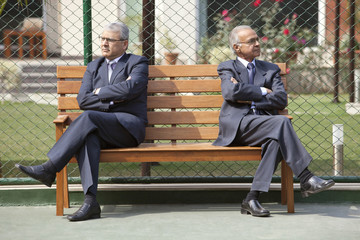 Senior male business executives looking away with arms crossed while sitting on bench in a tennis court