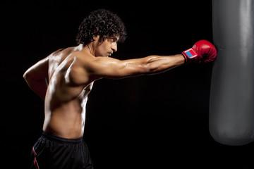 Young man hitting punching bag