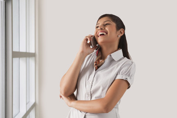 Cheerful young business woman enjoying the conversation on phone call