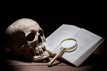 Human skull near old open book and magnifying glass on black background.