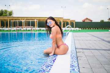 Sexy young woman sitting on the edge of a swimming pool, wearing bikini while on vacations in a sunny destination.
