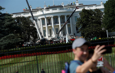 Tourists take pictures of themselves as construction cranes are set up while U.S. President Donald Trump is away on vacation from the White House in Washington