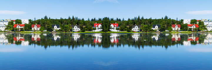 Typical summer view - cityscape of Reykjavik, capital of Iceland - lake shore with reflections in water.