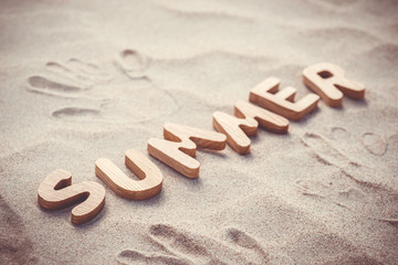 Summer. Wooden letters on the sand