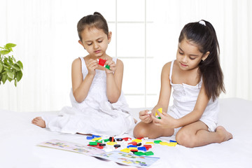 Girls solving puzzle while sitting on bed