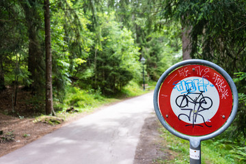 do not pass stop sign for bikes in forest with graffiti tags