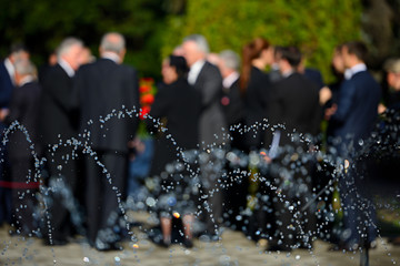 People in blur wearing black suits on funeral