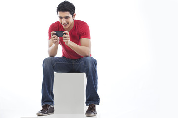 Full length of a man using phone for text messaging against white background