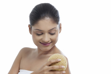 Close-up of smiling young woman using massage sponge