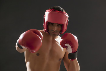 Portrait of male boxer wearing gloves and head protector isolated over black background