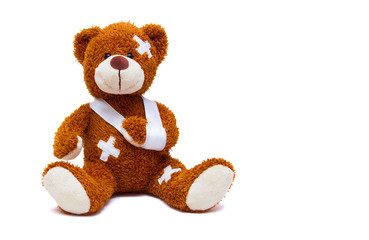 Injured teddy bear on white background