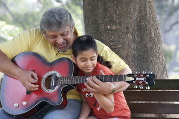 Grandfather teaching his granddaughter to play the guitar