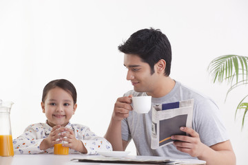 Father looking at daughter while having breakfast